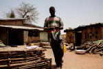 Susso, 38, walks through his compound in Dampha Kunda Village