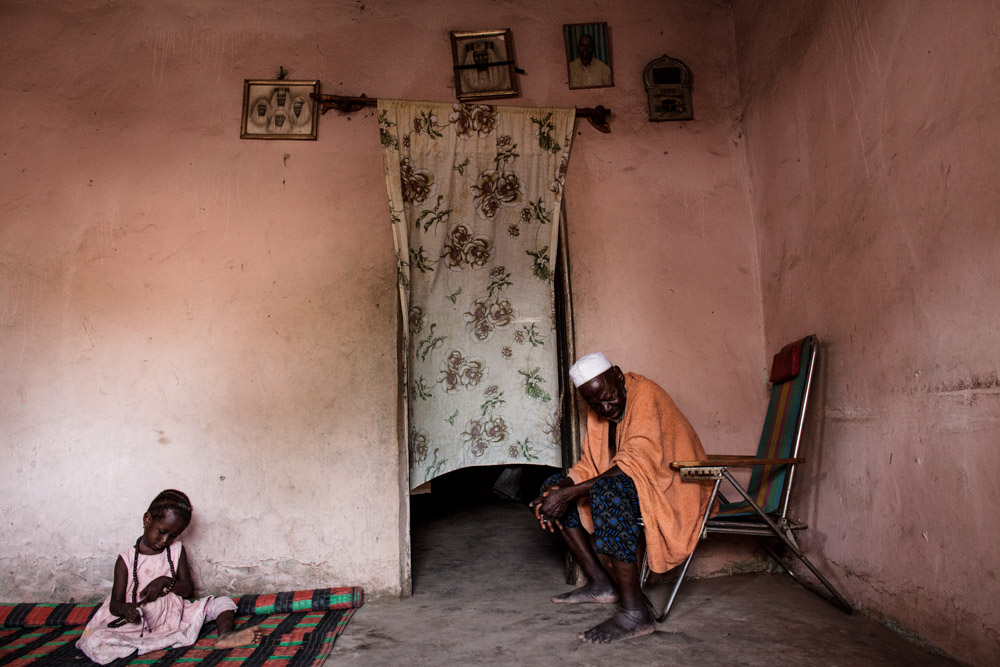 Seedy Ceesay, 70s, sits in his home next to his granddaughter Fatoumata, in Dampha Kunda Vilage, Gambia. Ceesay's first born son who took the {quote}back way{quote} to Europe but died in Libya due to an illness and his second son is in Europe now.