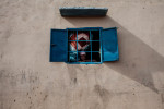 A young woman looks out the window of a home that was build with money sent from a relative living in Europe in Perai Village