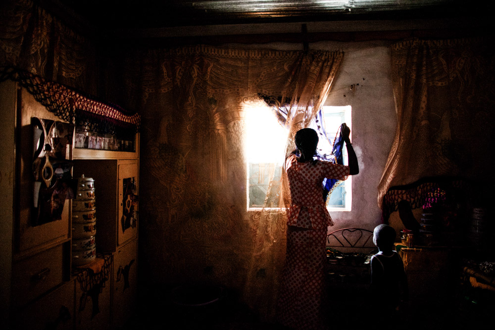 Dusu Fatty adjusts the curtains in her bedroom in the home built from money sent by her husband who lives in Spain, in Perai Village