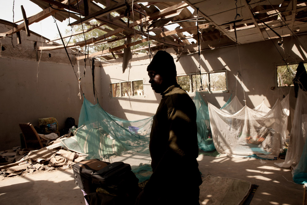 A policeman walks through a part of police headquarters destroyed by a Boko Haram suicide bomber in Kano, Nigeria. 2012