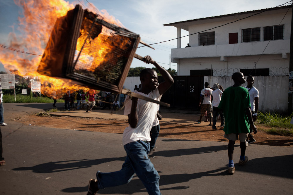 A man carries a burning stand after riots break out during a protest over runoff elections in Monrovia, Liberia