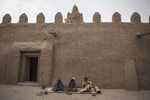 Men sit outside of the Sankore Mosque in Timbuktu, Mali on Monday, January 9, 2017. The Sakore Mosque was built in 1325 and is one of three learning centers in Timbuktu. It was partially destroyed during the occupation but has since been rebuilt.