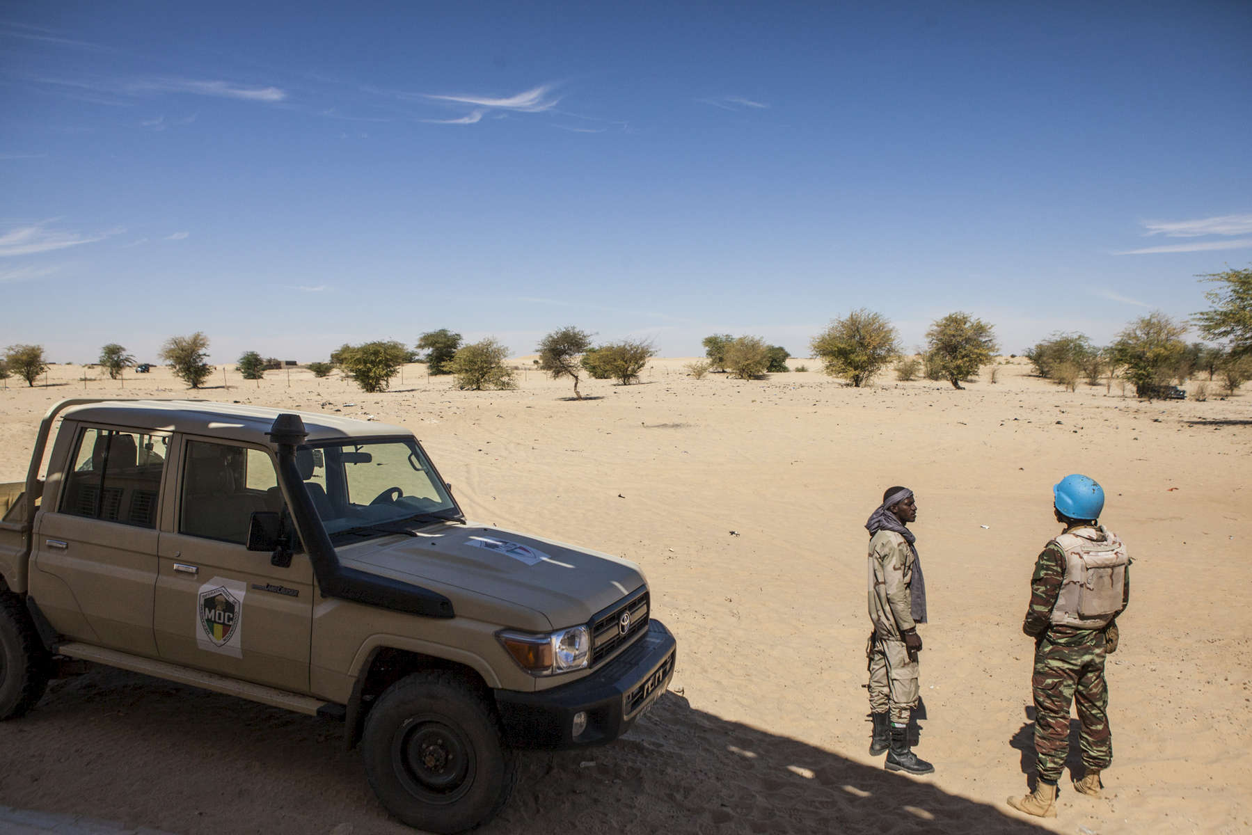 A United Nations peacekeeper speaks with a member of the MOC (Mécanisme Opérationnel de Coordination), a force comprised of members of the Malian Army as well as members of former armed rebel groups who are part of the peace process, on the outskirts of Timbuktu, Mali on Tuesday, January 10, 2017.