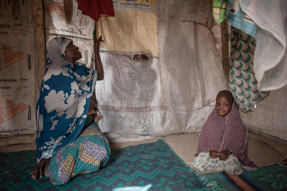 Hamsatu, 25, peaks through a tear in the divider of her tent while holding her one year old daughter Hauwa on her back, as she sits next to Fatima, 4-5, at Dalori Internally Displaced Persons Camp in Maiduguri, Nigeria.