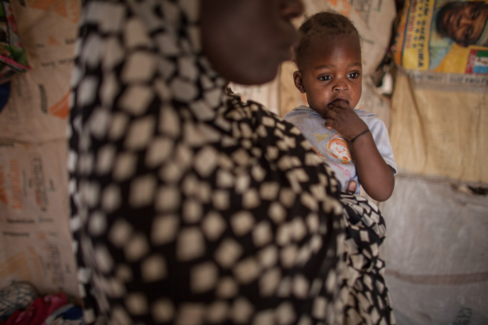 Halima, 15, holds Hauwa, 1, daughter of Hamsatu, in her tent at Dalori Internally Displaced Persons Camp in Maiduguri, Nigeria in March 2016. Halima was one of nine girls abducted from her compound just outside of Bama, four from her own family and five cousins. Later she escaped and was found by the Nigerian military and was finally brought to the Dalori IDP camp just outside of Maiduguri.