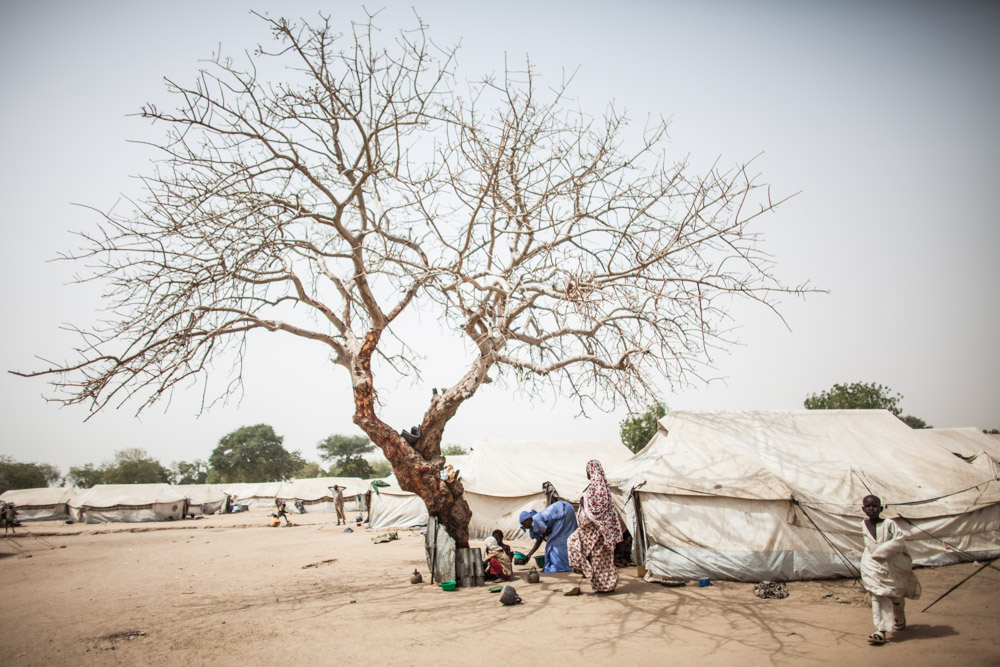 A woman feeds children taking shelter under a bare tree from the mid day sun at the Dalori Internally Displaced Persons Camp in Maiduguri, Nigeria. The Dalori IDP camp was established in March 2015 and holds close to 20,000 people from across Borno State. Maiduguri, the capitol, houses over 1.6 million displaced with over 100,000 in official camps and the rest living in host communities and informal camps across the city.