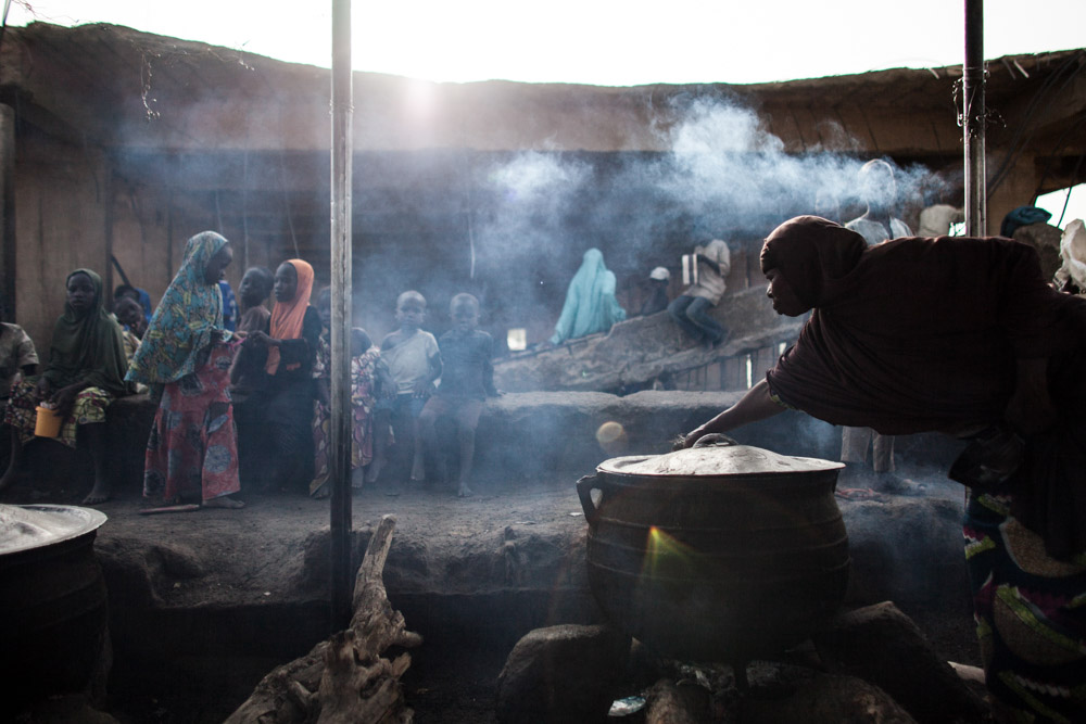 A woman prepares food at the children's kitchen at the Dalori Internally Displaced Persons Camp in Maiduguri, Nigeria. The Dalori IDP camp was established in March 2015 and holds close to 20,000 people from across Borno State. There are five kitchens total with one dedicated to children who are fed three times a day, including one school meal. Maiduguri, the capitol, houses over 1.6 million displaced with over 100,000 in official camps and the rest living in host communities and informal camps across the city.
