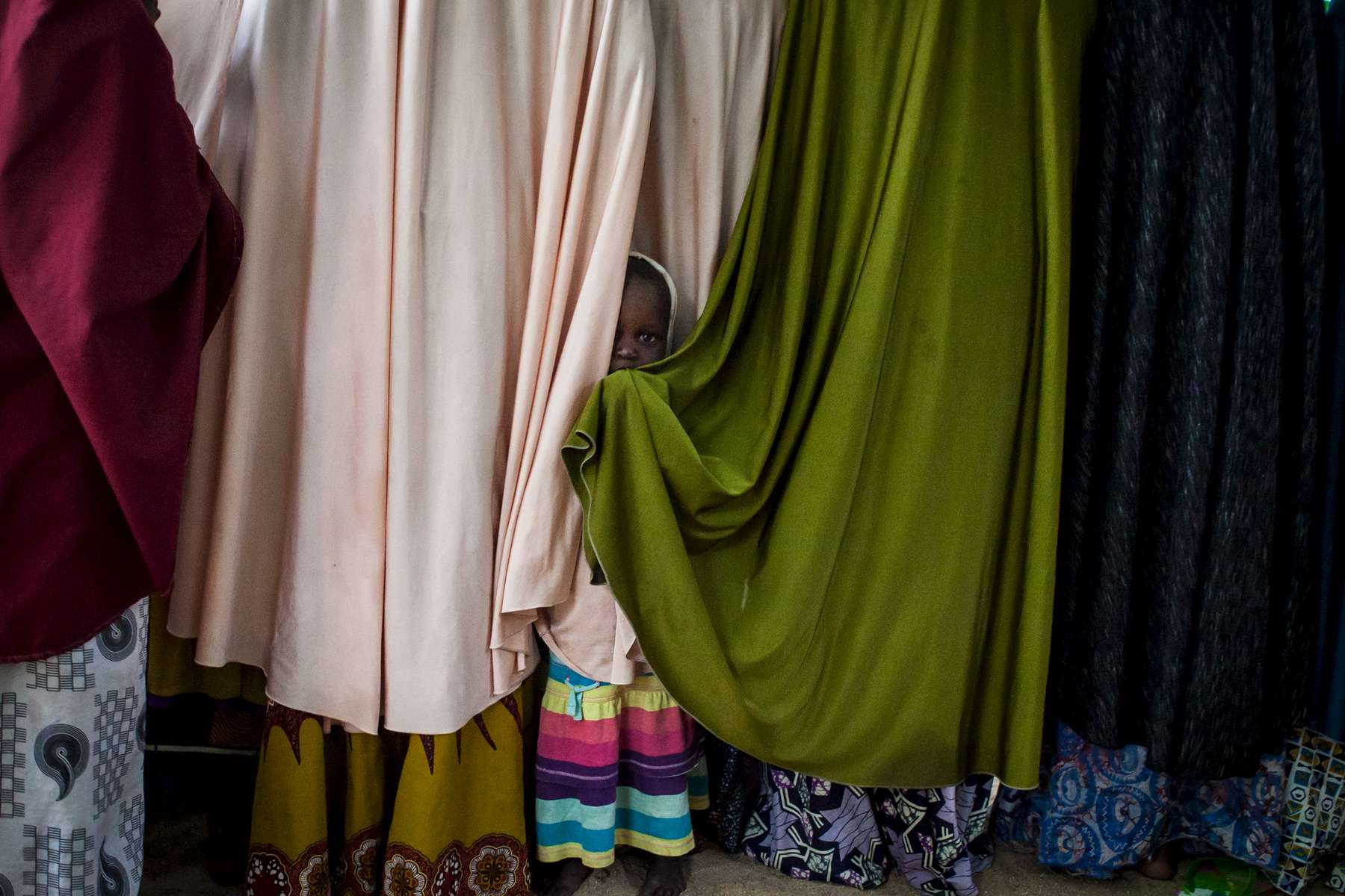 A young girl, whose mother was married to a Boko Haram commander, hides behind chadors at a detention center in Maiduguri, Nigeria on Thursday, June 16, 2016. The Nigerian military has detained hundreds of people, many are women and children, during their campaign against Boko Haram. Many innocent people have died while in custody while others are never heard from again.