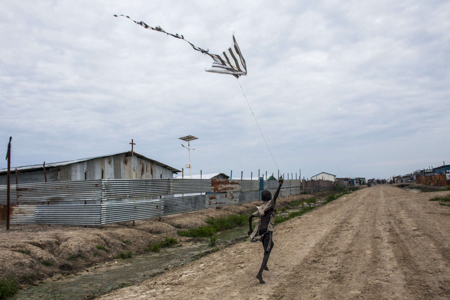 A boy flies a kite made from plastic bags in the Protection of Civilians (POC) site at the United Nations Mission in South Sudan (UNMISS) base in Malakal, South Sudan on Thursday, July 7, 2016. The POC site houses close to 32,000 displaced people mainly from the Shilluk and Nuer tribes in the Upper Nile State. In February of this year, violence broke out inside the camp as many armed members of the Dinka tribe, who resided in the camp at the time, along with members of the SPLA who infiltrated the camp, attacked the Shilluk and Nuer in the camp destroying large sections of the site resulting in many wounded and dead. The UN came under scrutiny due to the slow response of the peacekeepers to protect the civilians during the two day ordeal. During the violence, thousands demanded entrance into the UNMISS base at Charlie gate, seeking safety, but the opening of the gate was delayed for protection of the UN.