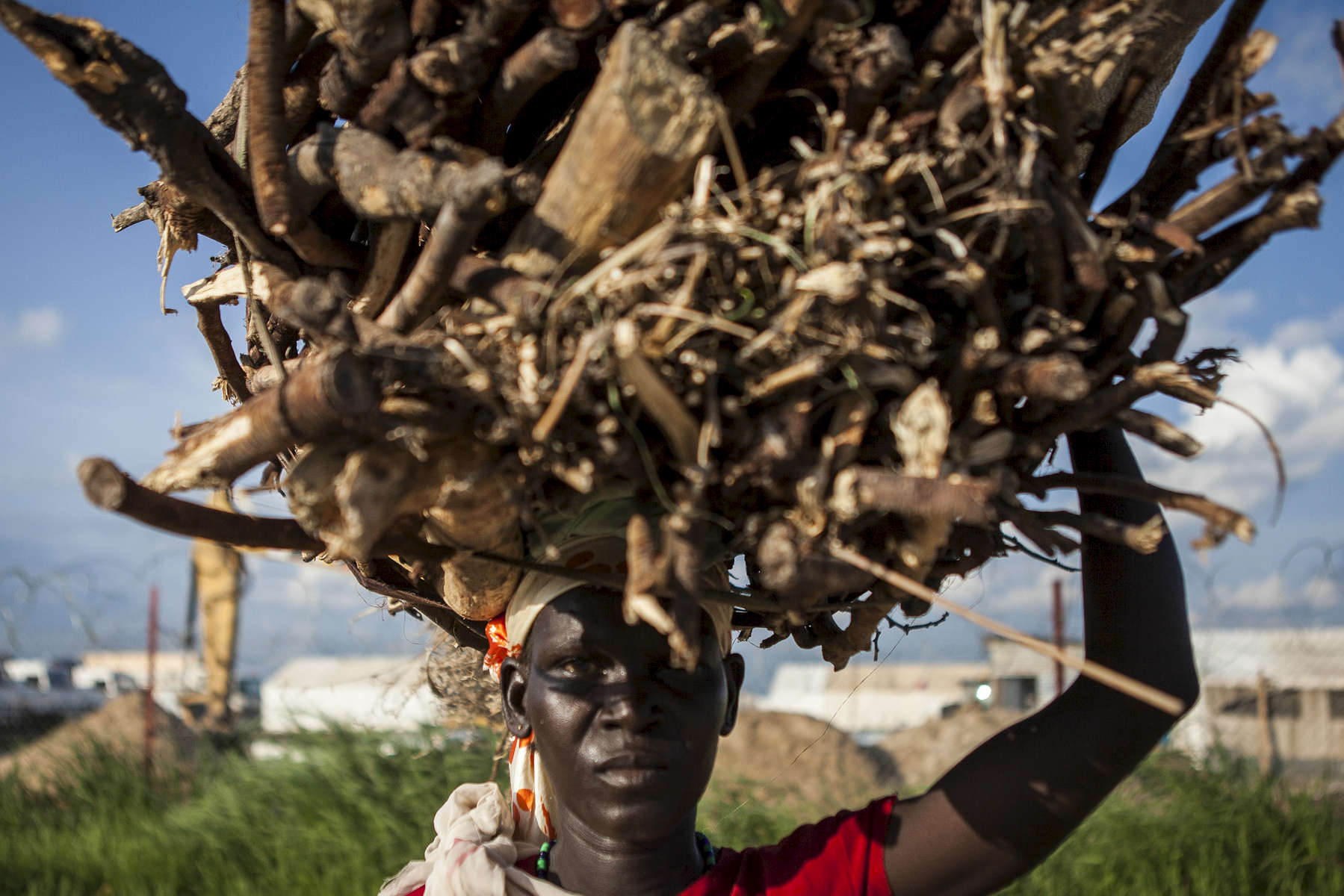 A woman carries firewood she collected outside the Protection of Civilians (POC) site at the United Nations Mission in South Sudan (UNMISS) in Malakal, South Sudan on Friday, July 8, 2016. Most women from the site gather firewood and sell goods outside of the compound as men fear tribal violence outside the protection of the UNMISS walls. Women still endure much harassment and attacks at the hands of the Dinka tribe members and the SPLA. The Malakal POC site houses over 32,000 displaced people mainly from the Shilluk and Nuer tribes. In February of this year, members of the Dinka tribe, who resided in the camp at the time, carried out a coordinated attack within the site leading to the destruction of hundreds of shelters and many deaths. Since then, most members of the Dinka tribe have fled to Malakal town where they occupy the homes of those still displaced.