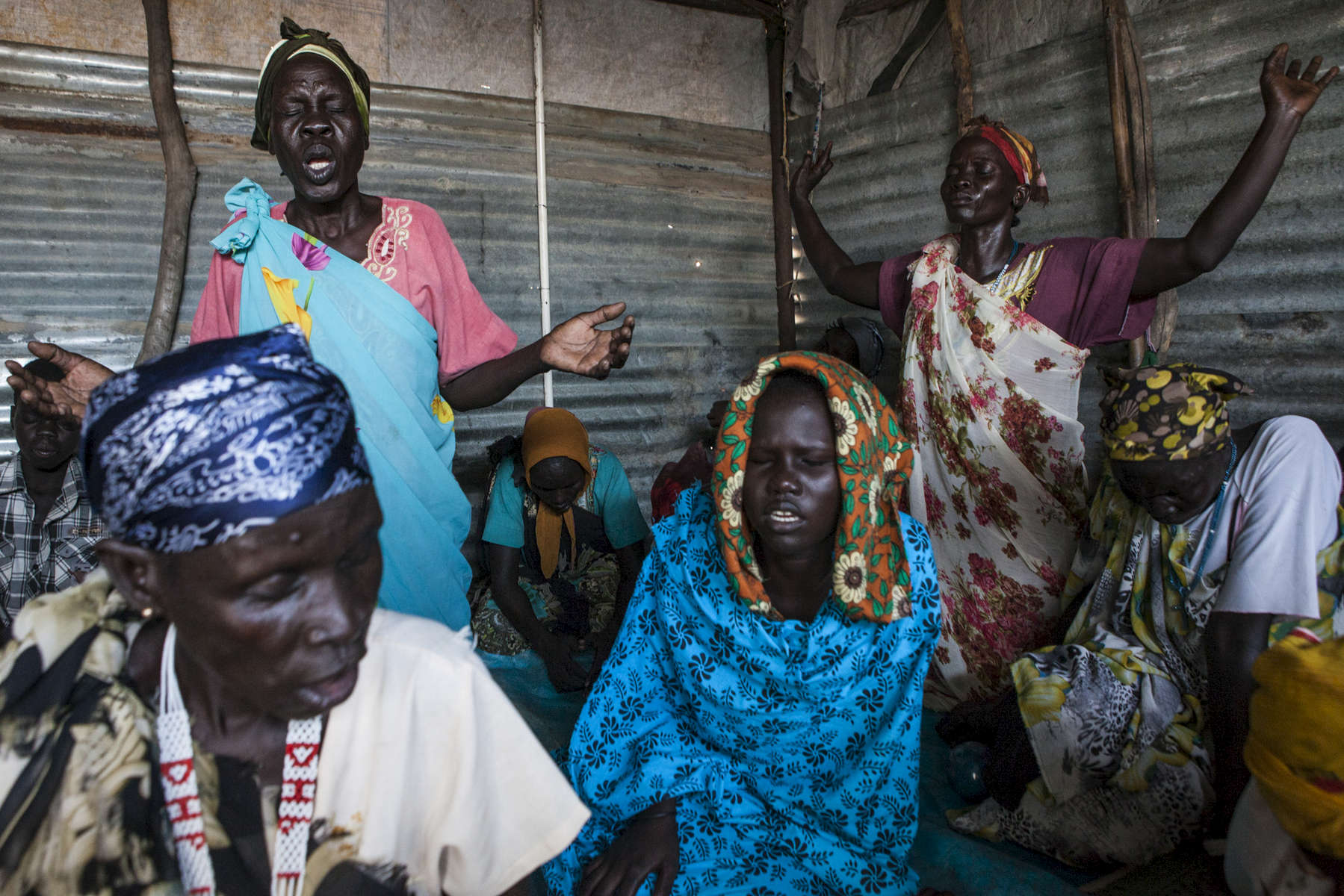 Women pray at a Pentecostal church in the Protection of Civilians (POC) site at the United Nations Mission in South Sudan (UNMISS) compound in Malakal, South Sudan on Saturday, July 9, 2016. The Malakal POC site houses over 32,000 displaced people mainly from the Shilluk and Nuer tribes. In February of this year, members of the Dinka tribe, who resided in the camp at the time, carried out a coordinated attack within the site leading to the destruction of hundreds of shelters and many deaths. Since then, most members of the Dinka tribe have fled to Malakal town where they occupy the homes of those still displaced.