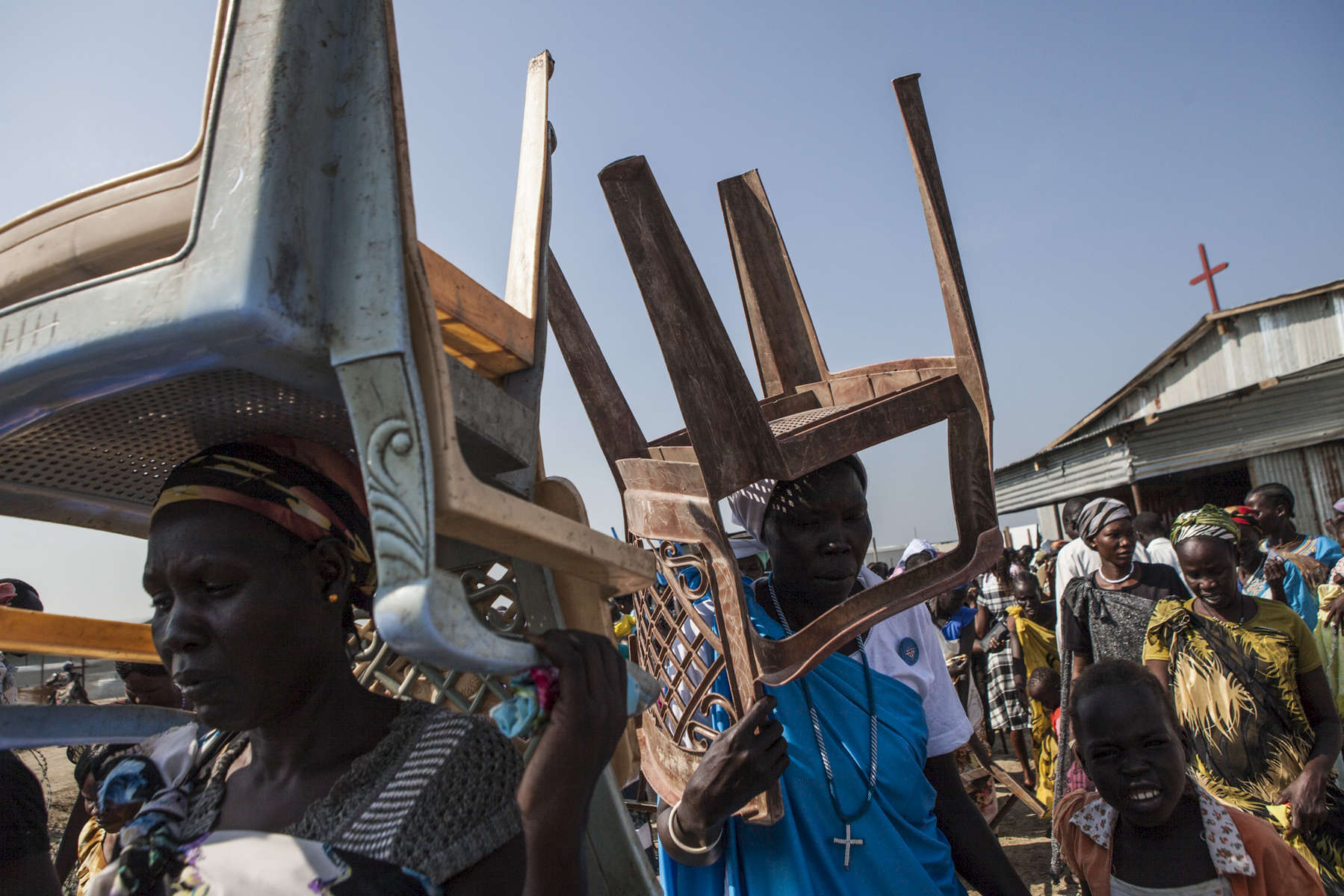 Church members carry out chairs and benches after service at the Dolieb Hill Presbyterian Church in the Protection of Civilians (POC) site at the United Nations Mission in South Sudan (UNMISS) compound in Malakal, South Sudan on Sunday, July 10, 2016. The Malakal POC site houses over 32,000 displaced people mainly from the Shilluk and Nuer tribes. In February of this year, members of the Dinka tribe, who resided in the camp at the time, carried out a coordinated attack within the site leading to the destruction of hundreds of shelters and many deaths. Since then, most members of the Dinka tribe have fled to Malakal town where they occupy the homes of those still displaced.