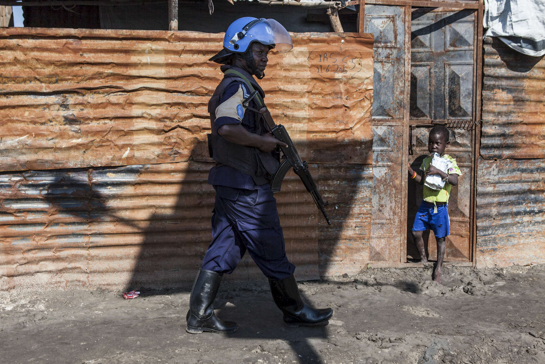 A member of the UN Police performs a search during a patrol in the Protection of Civilians (POC) site at the United Nations Mission in South Sudan (UNMISS) compound in Malakal, South Sudan on Tuesday, July 12, 2016. The Malakal POC site houses over 32,000 displaced people mainly from the Shilluk and Nuer tribes. In February of this year, members of the Dinka tribe, who resided in the camp at the time, carried out a coordinated attack within the site leading to the destruction of hundreds of shelters and many deaths. Since then, most members of the Dinka tribe have fled to Malakal town where they occupy the homes of those still displaced.