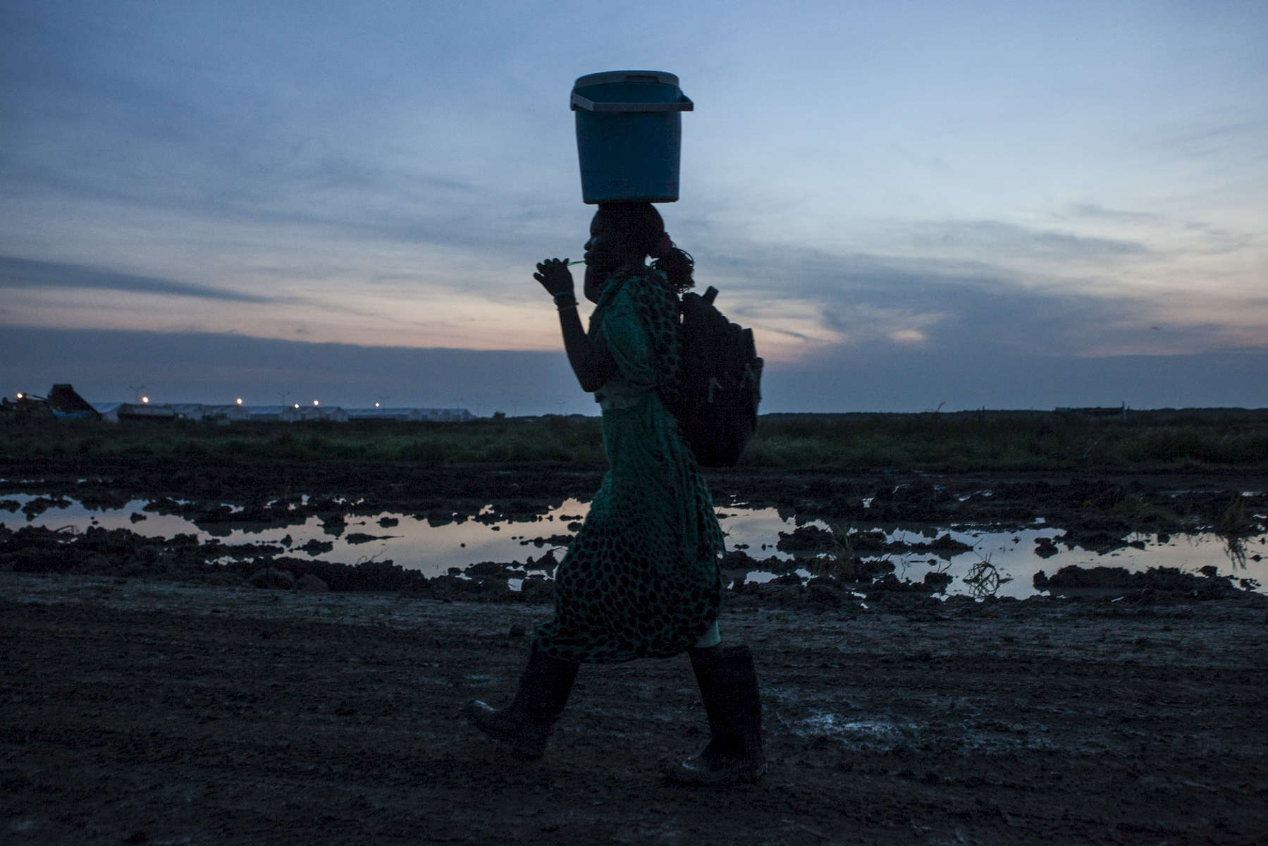 A woman brushes her teeth at dawn while leaving the camp to farm outside the Protection of Civilians (POC) site at the United Nations Mission in South Sudan (UNMISS) compound in Malakal, South Sudan on Wednesday, July 13, 2016. The Malakal POC site houses over 32,000 displaced people mainly from the Shilluk and Nuer tribes. In February of this year, members of the Dinka tribe, who resided in the camp at the time, carried out a coordinated attack within the site leading to the destruction of hundreds of shelters and many deaths. Since then, most members of the Dinka tribe have fled to Malakal town where they occupy the homes of those still displaced.