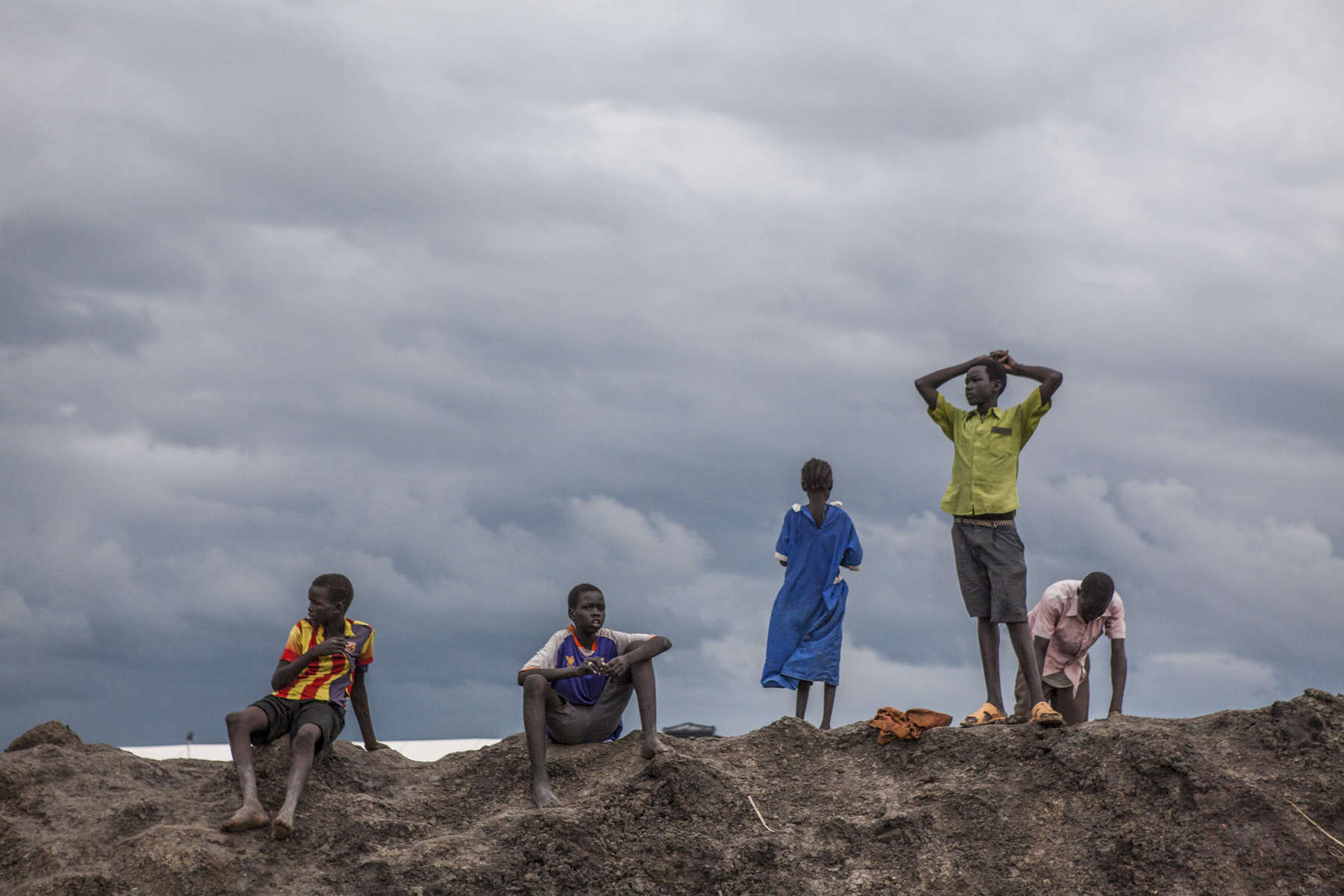 Children stand on top of a berm at the Protection of Civilians (POC) site at the United Nations Mission in South Sudan (UNMISS) compound in Malakal, South Sudan on Wednesday, July 13, 2016. The Malakal POC site houses over 32,000 displaced people mainly from the Shilluk and Nuer tribes. In February of this year, members of the Dinka tribe, who resided in the camp at the time, carried out a coordinated attack within the site leading to the destruction of hundreds of shelters and many deaths. Since then, most members of the Dinka tribe have fled to Malakal town where they occupy the homes of those still displaced.