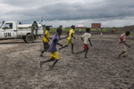 Boys play soccer in front of UN Peacekeepers at the Protection of Civilians (POC) site at the United Nations Mission in South Sudan (UNMISS) compound in Malakal, South Sudan on Wednesday, July 13, 2016. The Malakal POC site houses over 32,000 displaced people mainly from the Shilluk and Nuer tribes. In February of this year, members of the Dinka tribe, who resided in the camp at the time, carried out a coordinated attack within the site leading to the destruction of hundreds of shelters and many deaths. Since then, most members of the Dinka tribe have fled to Malakal town where they occupy the homes of those still displaced.