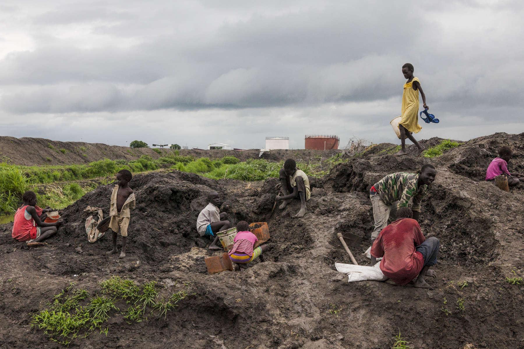 Children collect dirt to reinforce their shelters during the rainy season at the Protection of Civilians (POC) site at the United Nations Mission in South Sudan (UNMISS) compound in Malakal, South Sudan on Wednesday, July 13, 2016. The Malakal POC site houses over 32,000 displaced people mainly from the Shilluk and Nuer tribes. In February of this year, members of the Dinka tribe, who resided in the camp at the time, carried out a coordinated attack within the site leading to the destruction of hundreds of shelters and many deaths. Since then, most members of the Dinka tribe have fled to Malakal town where they occupy the homes of those still displaced.