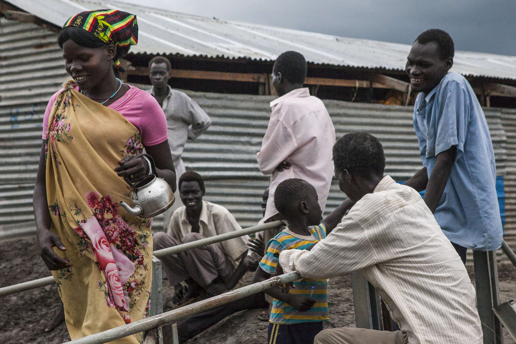 A group of people gather at a small bridge at the Protection of Civilians (POC) site at the United Nations Mission in South Sudan (UNMISS) compound in Malakal, South Sudan on Wednesday, July 13, 2016. The Malakal POC site houses over 32,000 displaced people mainly from the Shilluk and Nuer tribes. In February of this year, members of the Dinka tribe, who resided in the camp at the time, carried out a coordinated attack within the site leading to the destruction of hundreds of shelters and many deaths. Since then, most members of the Dinka tribe have fled to Malakal town where they occupy the homes of those still displaced.