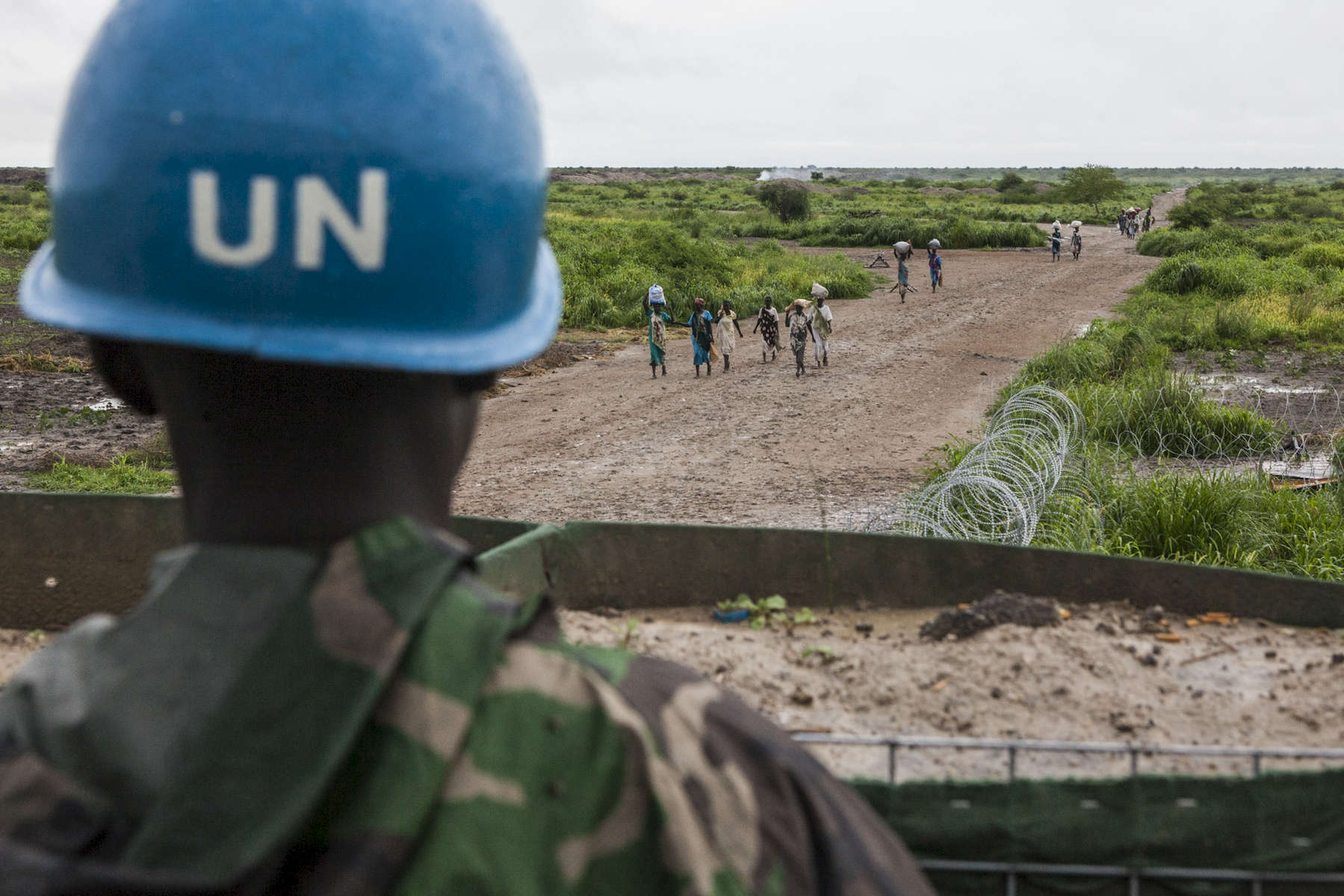 A UN Peacekeeper stands guard at an outpost as civilians enter the Protection of Civilians (POC) site outside the United Nations Mission in South Sudan (UNMISS) compound in Malakal, South Sudan on Wednesday, July 13, 2016. The Malakal POC site houses over 32,000 displaced people mainly from the Shilluk and Nuer tribes. In February of this year, members of the Dinka tribe, who resided in the camp at the time, carried out a coordinated attack within the site leading to the destruction of hundreds of shelters and many deaths. Since then, most members of the Dinka tribe have fled to Malakal town where they occupy the homes of those still displaced. The UN has assured the displaced people that increased security measures around the camp will protect them from any further attack. Most of the displace are not convinced.