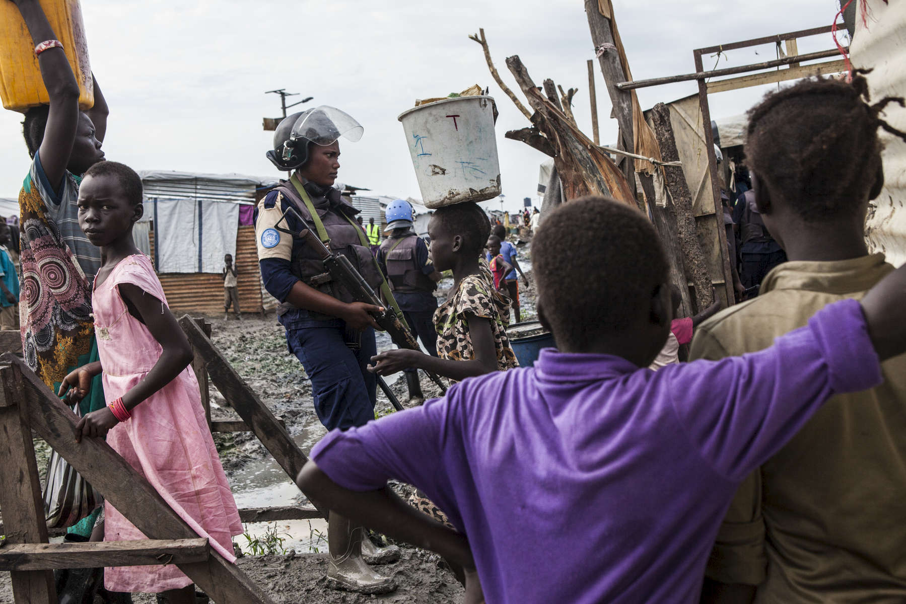A member of the United Nations Police, UNPOL, stands guard during a routine search of contraband of the Protection of Civilians (POC) site at the United Nations Mission in South Sudan (UNMISS) compound in Malakal, South Sudan on Friday, July 15, 2016. The Malakal POC site houses over 32,000 displaced people mainly from the Shilluk and Nuer tribes. In February of this year, members of the Dinka tribe, who resided in the camp at the time, carried out a coordinated attack within the site leading to the destruction of hundreds of shelters and many deaths. Since then, most members of the Dinka tribe have fled to Malakal town where they occupy the homes of those still displaced. The UN has assured the displaced people that increased security measures around the camp will protect them from any further attack. Most of the displace are not convinced.