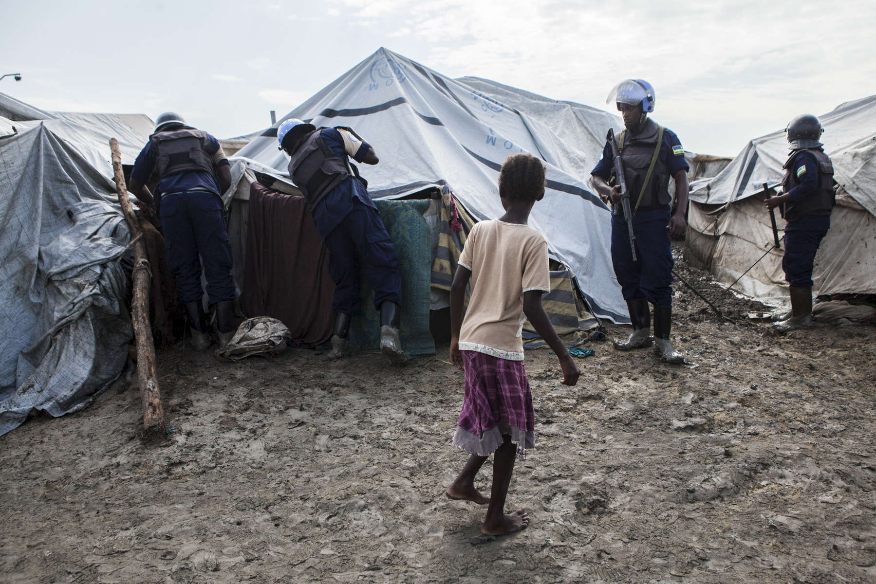 A young girl watches as members of the United Nations Police, UNPOL, searches shelters for contraband in the Protection of Civilians (POC) site at the United Nations Mission in South Sudan (UNMISS) compound in Malakal, South Sudan on Friday, July 15, 2016. The Malakal POC site houses over 32,000 displaced people mainly from the Shilluk and Nuer tribes. In February of this year, members of the Dinka tribe, who resided in the camp at the time, carried out a coordinated attack within the site leading to the destruction of hundreds of shelters and many deaths. Since then, most members of the Dinka tribe have fled to Malakal town where they occupy the homes of those still displaced. The UN has assured the displaced people that increased security measures around the camp will protect them from any further attack. Most of the displace are not convinced.