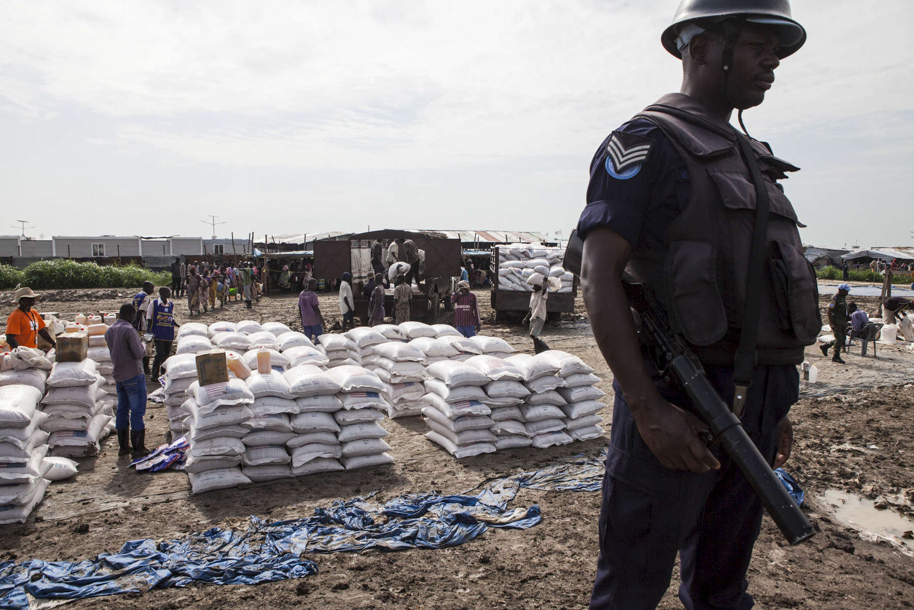 A member of the United Nations Police, UNPOL, stands guard during a World Food Program food distribution in the Protection of Civilians (POC) site at the United Nations Mission in South Sudan (UNMISS) compound in Malakal, South Sudan on Friday, July 15, 2016. The Malakal POC site houses over 32,000 displaced people mainly from the Shilluk and Nuer tribes. In February of this year, members of the Dinka tribe, who resided in the camp at the time, carried out a coordinated attack within the site leading to the destruction of hundreds of shelters and many deaths. Since then, most members of the Dinka tribe have fled to Malakal town where they occupy the homes of those still displaced. The UN has assured the displaced people that increased security measures around the camp will protect them from any further attack. Most of the displace are not convinced.