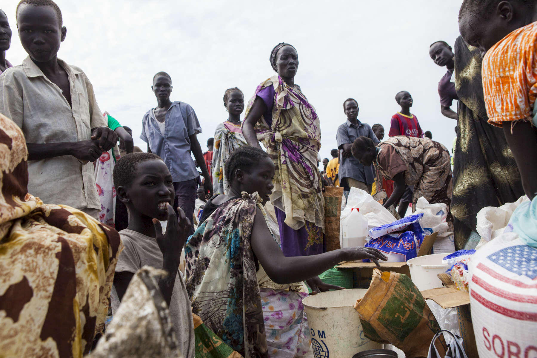 People gather to divide supplies at the World Food Program food distribution in the Protection of Civilians (POC) site at the United Nations Mission in South Sudan (UNMISS) compound in Malakal, South Sudan on Friday, July 15, 2016. The Malakal POC site houses over 32,000 displaced people mainly from the Shilluk and Nuer tribes. In February of this year, members of the Dinka tribe, who resided in the camp at the time, carried out a coordinated attack within the site leading to the destruction of hundreds of shelters and many deaths. Since then, most members of the Dinka tribe have fled to Malakal town where they occupy the homes of those still displaced. The UN has assured the displaced people that increased security measures around the camp will protect them from any further attack. Most of the displace are not convinced.