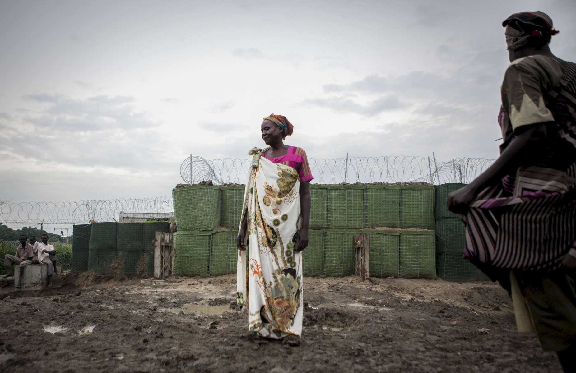 Rachael Mayik stands outside a now barricaded Charlie Gate in the Protection of Civilians (POC) site at the United Nations Mission in South Sudan (UNMISS) compound in Malakal, South Sudan on Saturday, July 16, 2016. Charlie Gate is the site where thousands of people gathered during the violence that erupted in February of this year. The UN came under scrutiny due to the slow response of the peacekeepers to protect the civilians during the two day ordeal. During the violence, thousands demanded entrance into the UNMISS base at Charlie gate, seeking safety, but the opening of the gate was delayed for protection of the UN compound. The Malakal POC site houses over 32,000 displaced people mainly from the Shilluk and Nuer tribes. In February of this year, members of the Dinka tribe, who resided in the camp at the time, carried out a coordinated attack within the site leading to the destruction of hundreds of shelters and many deaths. Since then, most members of the Dinka tribe have fled to Malakal town where they occupy the homes of those still displaced.