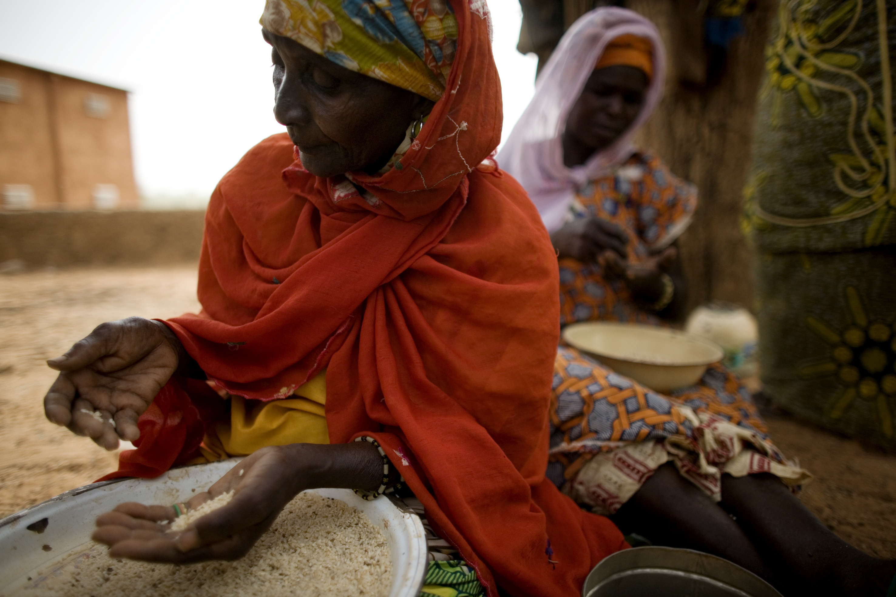 Zaina Bou Bondaire and Fatima Souley pick out rocks and dirt from rice found on the ground outside of the OPVN, Office des Produits Vivriers du Niger, food storage warehouse in Niamey, Niger