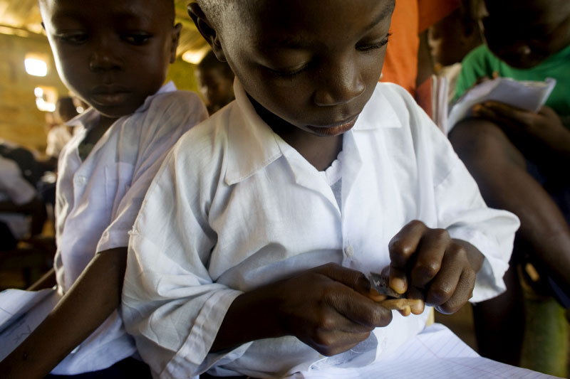 A young boy sharpens his pencil during class at the Varfley Junior High School in Kingsville, Liberia.