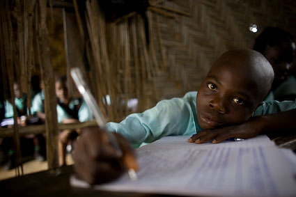 Amos Clark, 14 takes notes at the Eric Z. Zinnah Community School in Bomi, Liberia