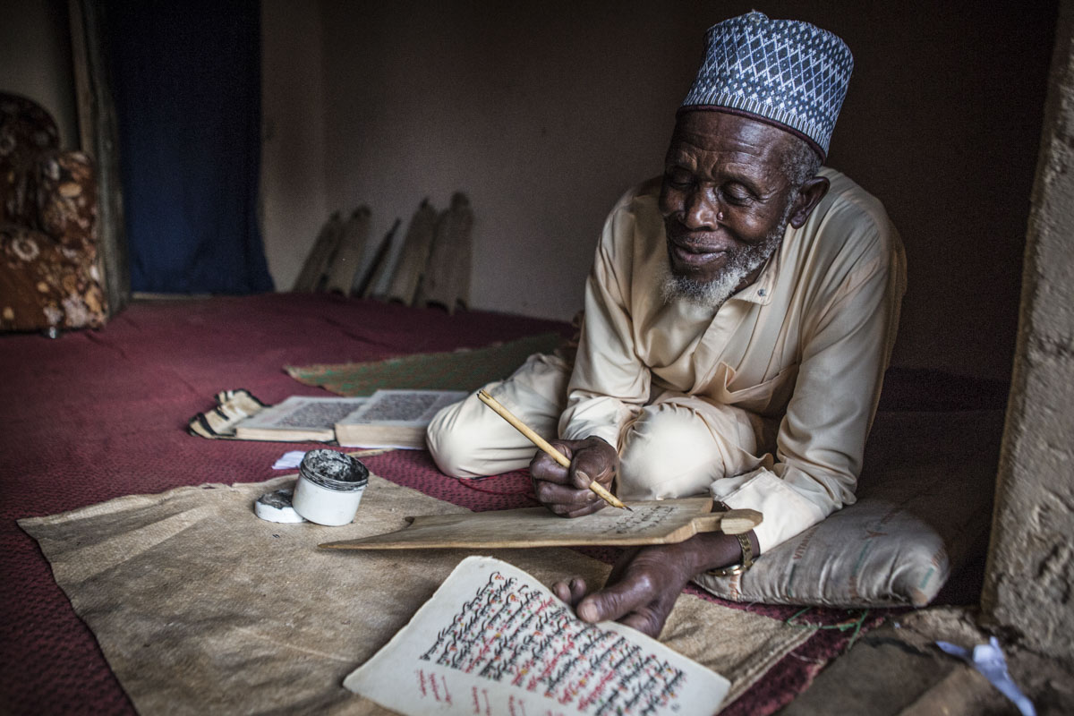 Barkin Ladi, Jos, Nigeria- Imam Abubakar Abdullahi writes on a tablet at his home in Yelwa Village Barkin Ladi, Nigeria on Tuesday, October 23, 2018. After the June attack in Gashish District that destroyed Nghar Village, many of the displaced fled to neighboring Yelwa Village where Imam Abubakar Abdullahi saved over 300 lives. Over one thousand people have lost their lives this year due to an ongoing conflict between farmers and herders. The current crisis reflects the country's woes from over-population, poverty and climate change to religious division and ethnic favoritism. Growing animosity between ethnic groups coupled with a lack of security  has fomented this increase in violence in recent years. Despite the divisive chaos engulfing the Middle Belt of Nigeria, a group of multi-ethnic men and women, part of the Vigilante Group of Nigeria, are providing much needed security and trust to all groups affected by the conflict.