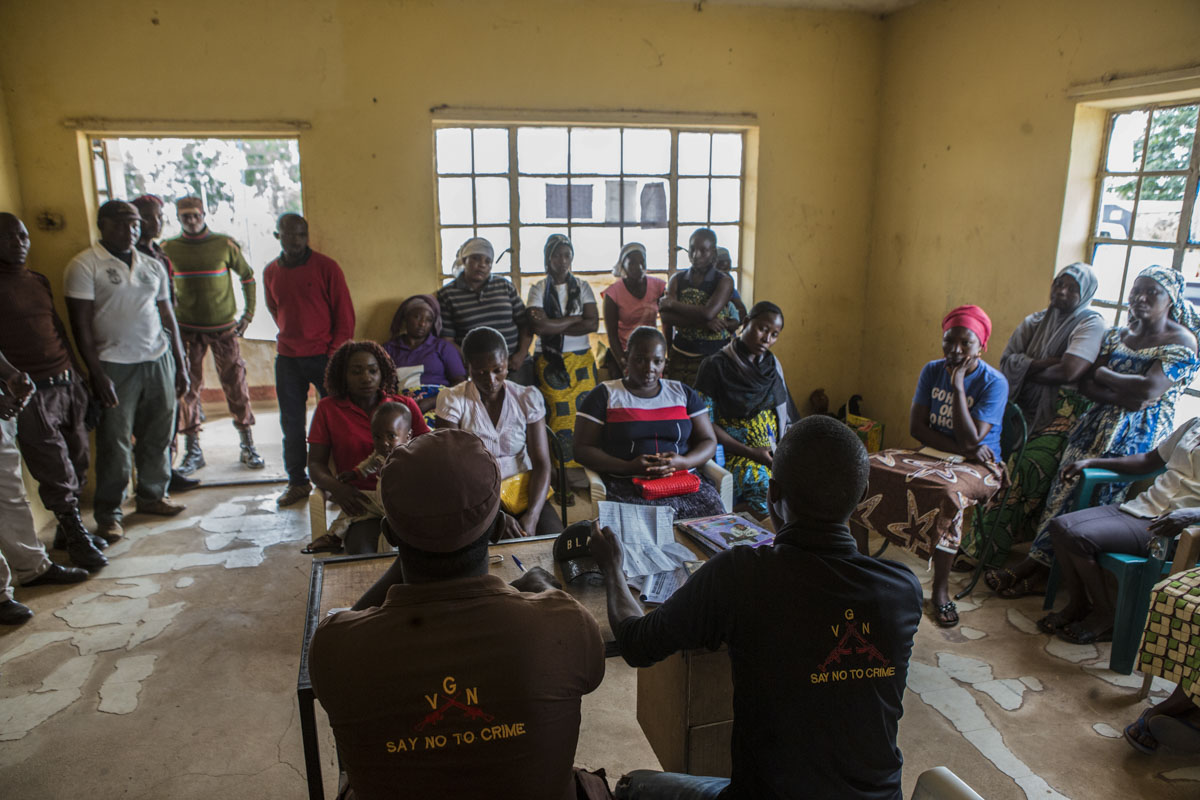 Barkin Ladi, Jos, Nigeria- Members of the Vigilante Group of Nigeria, Barkin Ladi Division mediate a dispute over chickens within the group Women for Women at their headquarters in Barkin Ladi, Nigeria on Thursday, October 25, 2018. Nationally, the Vigilante Group of Nigeria numbers at 300,000 members, with Plateau State holding the most at 17,300 according to the National Administration Office. Barkin Ladi is the most active division nationwide.Over one thousand people have lost their lives this year due to an ongoing conflict between farmers and herders. The current crisis reflects the country's woes from over-population, poverty and climate change to religious division and ethnic favoritism. Growing animosity between ethnic groups coupled with a lack of security  has fomented this increase in violence in recent years. Despite the divisive chaos engulfing the Middle Belt of Nigeria, a group of multi-ethnic men and women, part of the Vigilante Group of Nigeria, are providing much needed security and trust to all groups affected by the conflict.