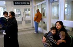 Nafisa Zulfiqar, 26, left, holding her daughter Heena Ahmed, 13 months, walks nervously at the Canadian Immigration office waiting area as her husband Zulfiqar and her oldest son Abdul, 12, are interviewed inside by Canadian immigration officials. Zulfiqar Ahmed's cousin, Kishwer Sultana, 28, right, waits with her children Humza, 11 months, right, and Zain, 2.