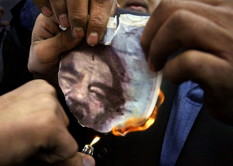 On the streets of Dearborn, Iraqis burn a photo of the deposed Iraqi president in front of the Karbalaa Islamic Education Center on Warren Avenue, in Dearborn, Michigan. The city has a large Arab-American population and news of Saddam Hussein's capture brought demonstrators out is celebration.