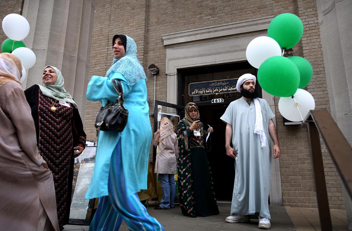 Javier Azhar Graviz of North Bergen, New Jersey, 24, right, native of Uruguay, waits for his friends outside of the Islamic Educational Center of North Hudson in Union City, New Jersey, during the Fourth Annual Hispanic Muslim Day. The annual event is organized to introduce Hispanics to Islam. Graviz, who was brought up Catholic, converted to Islam seven years ago.