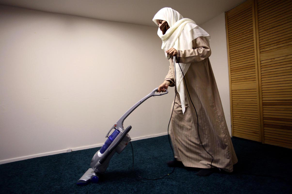 Gaby Gonzalez, 20, vacuums her apartment in Paterson, New Jersey. Gonzalez, native of Honduras, grew up Catholic and converted to Islam in December 2005. Gonzalez's husband installed green carpet in their living room to make it a prayer room. Green color is used in many mosques. Gonzalez said it was the favorite color of Prophet Muhammad. Gonzalez and her husband try to live a simple life, free of worldly possessions.