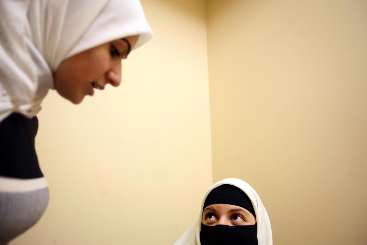 Hispanic Muslim convert Gaby Gonzalez, 20, right, speaks with a co-worker at Medina Group, an Islamic advertising company, in Clifton, New Jersey, Sep. 21, 2006. Gonzalez, native of Honduras, grew up Catholic and converted to Islam in December 2005.