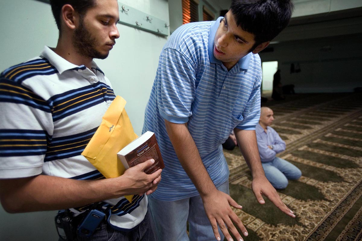 Imran Ali Shah of West Paterson, right, shows new convert Chris Rivera of Union City, left, how to pray for the first time after Rivera made his Shahada or declaration of faith at the Islamic Educational Center of North Hudson in Union City, New Jersey, Sep. 19, 2006. Rivera works for Shah's parents and was introduced to Islam while working for them.