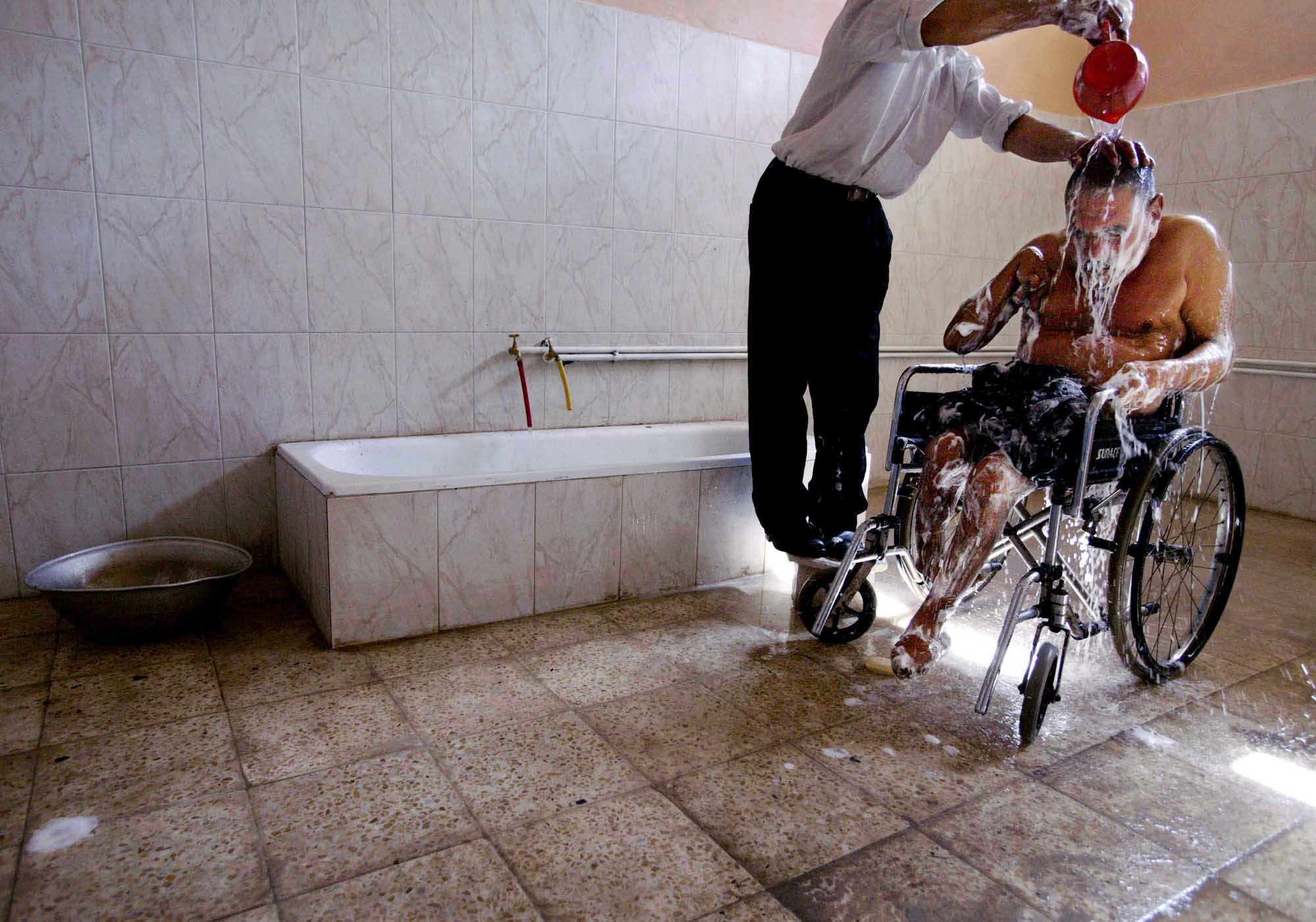 Abass Chechan, 33, left, gives a bath to Hamza Saheb, 65. Chechan worked as a private in the old Iraqi army. {quote}When I see patients who are dirty, I feel it is my duty to help them,{quote} said Chechan.