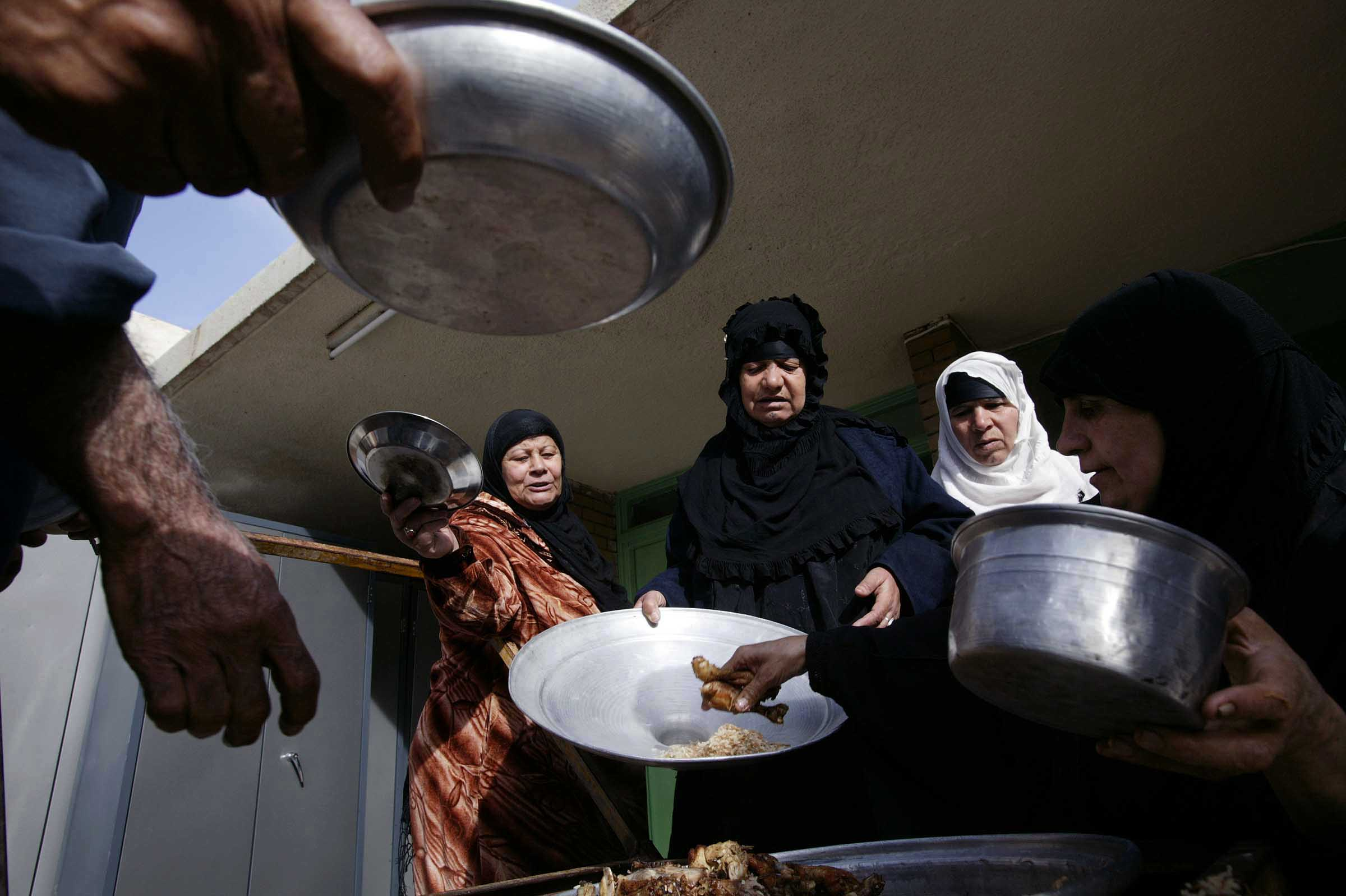 Nursing home residents gather around Hamdeya Mehdi, 40, right, who is serving chicken and rice. Once a month Mehdi does Zakat or charity to the poor.