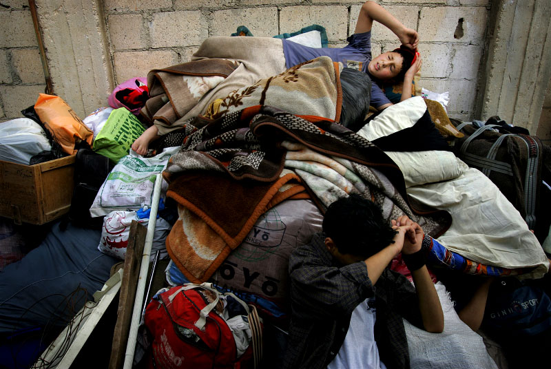 Abdula Abdul Aziz, 10, on top of a pile of his family's belongings, and his brother Bader Aziz, 15, sitting on the ground, rest as they are moving to a new apartment because they were evicted. Jordanian landlord didn't want a family of ten living in one room apartment.