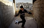 Abed Al Rahman Abdul Aziz, 10, plays alone on the porch of his home in Amman, Jordan. Abed Al Rahman can't go to school because Jordan doesn't allow Iraqi children to attend public school and his parents can't afford to send him to a private school.