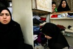 Somaya Abdul Aziz, 28, left, talks to her mother as her sister Hala, 18, second from left, picks out clothes from a refrigerator that the family uses as a closet outside their apartment in Amman, Jordan. The family doesn't have any closets and their fridge is broken.