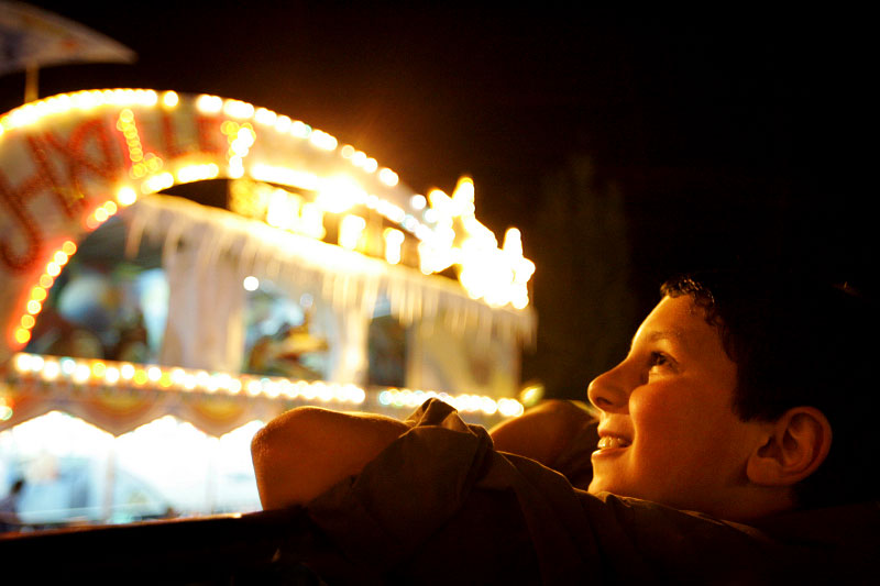 Abdula Abdul Aziz, 10, of Ramadi, Iraq, enjoys the lights at the Jibeaha Amusement Park in Amman, Jordan.