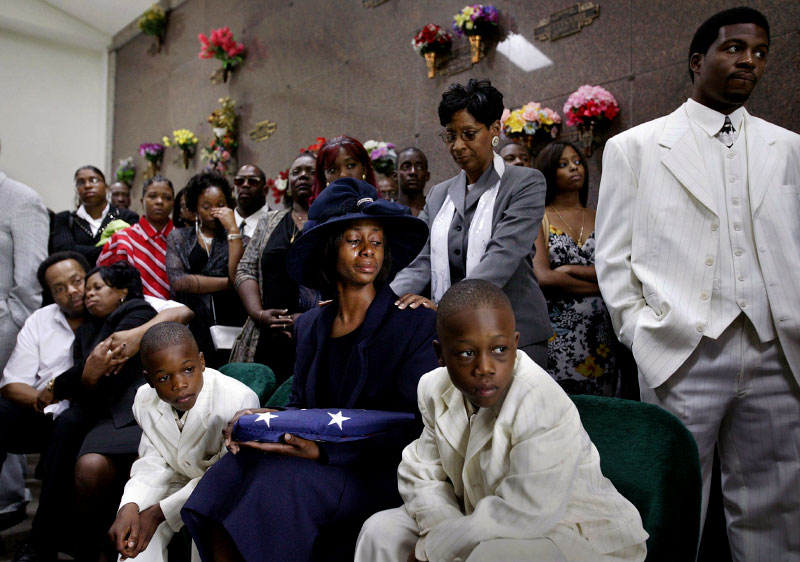 Orepa Daniels, sitting with her sons, Kevin, 8, left, and Kenneth III, 9, reacts after a 21-gun salute at the funeral for her husband, Detroit Police Officer Kenneth Daniels Jr., 28, at Mt. Hope Memorial Gardens in Livonia, Michigan. Daniels, 28, was shot and killed in southwest Detroit while working off-duty as a security guard at the Sting topless bar to be able to buy a new condominium for his family.