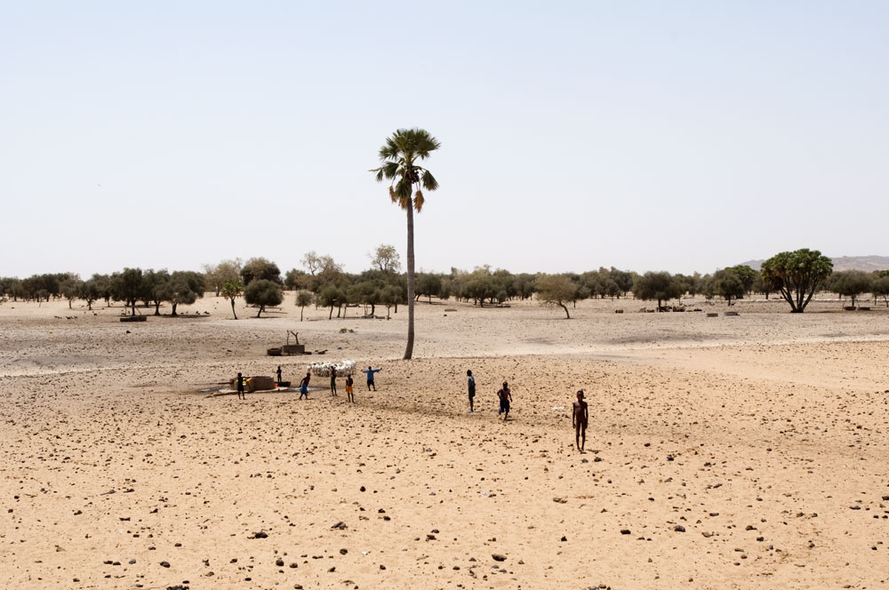 Children at a well used by migrating livestock in a parched landscape in Guidimakha province.Guidimakha, Mauritania.Photo © J.B. Russell