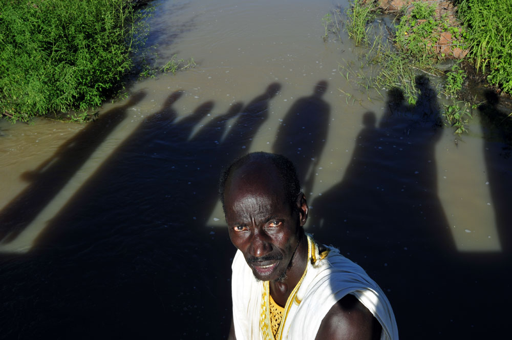 A man from a Moor village on a dam constructed with the support of the French NGO the GRDR. The dam  extends the brief planting season and improves water management in this part of the Western Sahel region.Seibath, Mali.Photo © J.B. Russell