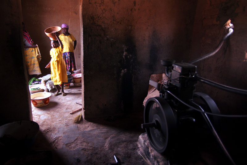 Women bring their sorghum, millet and corn to be milled into flour at the village mill. The village women's collective {quote}Manegre{quote} worked together to get the mill installed in the village, saving them hours of grinding the grains into flour by hand.Tanlili, Burkina Faso.Photo © J.B. Russell